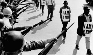 "image of protesters demonstrating against Jim Crow laws, carrying signs stating ""I am a man"" while soldiers point their riles with bayonets at them."