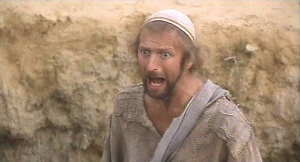 still image from the movie Life of Brian. A man with an aghast, outraged expression on his face is captured with his mouth wide open in an expression of outrage.